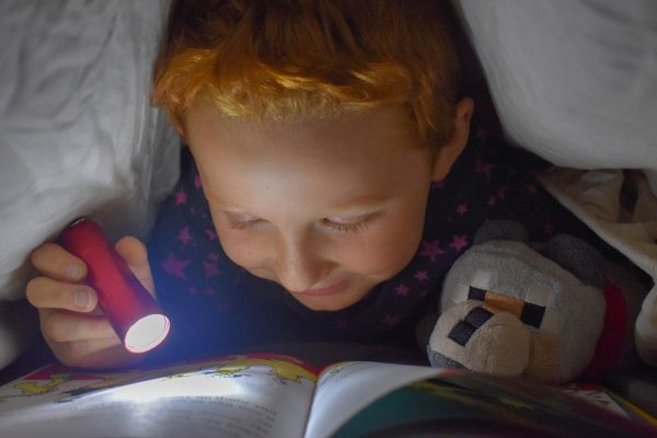 Child Reading Under a Down Comforter